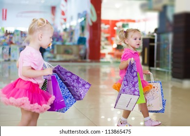 Elegant little girls in a big shopping center posing on the background shop windows.