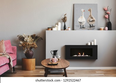 Elegant living room interior with black and grey fireplace, wooden coffee table and pink couch