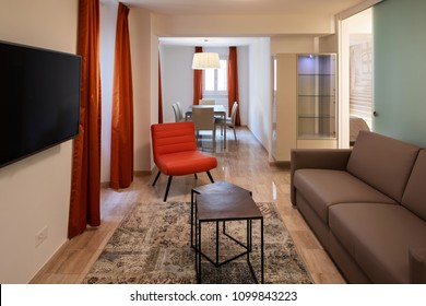 Elegant living room with leather sofa and a red designer armchair. nobody inside