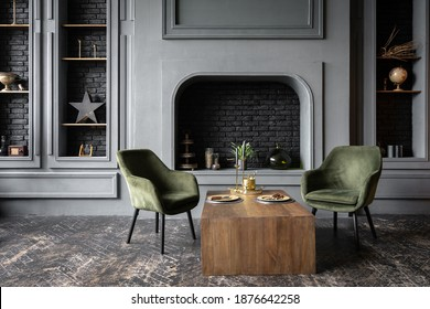 Elegant living room with loft interior design, comfort armchairs near wooden table against decorative fireplace and home decor in fancy apartment - Shutterstock ID 1876642258