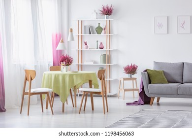 Elegant living room with wooden chairs, round table with olive green tablecloth, grey couch with pillow and heather in pots