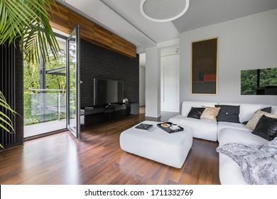 Elegant living room with wooden floor with balcony door open to spacious terrace