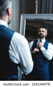 Elegant look. Full length of handsome man in full suit adjusting his jacket while standing in front of the mirror indoors