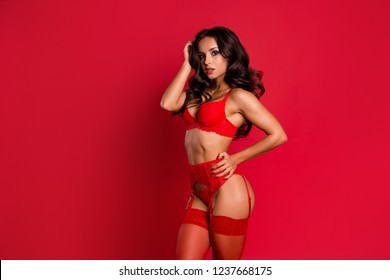 Elegant, lovely, cute, sweet, gorgeous, stylish, stunning, adorable lady in boudoir lace on suspenders with modern wavy hair stand half turn isolated on bright red background