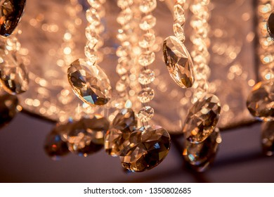 Elegant and luxurious glass decorations on the chandelier, illuminated by bright light with a lot of highlights and beautiful bokeh