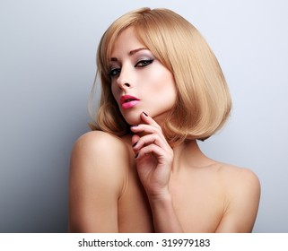 Elegant makeup blond woman with manicured nails posing on blue background