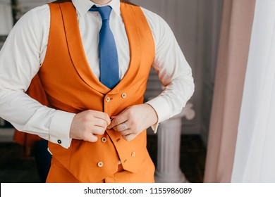 Elegant male groom buttons up orange waistcoat, dressed in festive clothes, prepares for wedding ceremony, poses indoor alone. Fashionable man in orange suit. Wedding and celebration concept