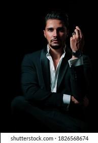 elegant male model wearing a black blazer and a white shirt on a black background