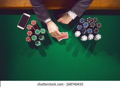 Elegant male poker player with smartphone looking at his cards with piles of chips all around