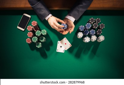 Elegant male poker player with smartphone holding chips, he has two ace cards, hands close up top view
