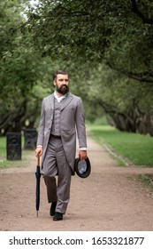 An elegant man in a 19th century suit walks in the Park