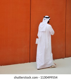 an elegant man of Arab ethnicity with sunglasses walks the streets of his country