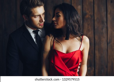 Elegant man in a black suit. Couple at home. Hot woman in a red dress