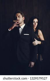 Elegant man in a black suit. Couple at home. Hot woman in a black underwear. Male with cigar