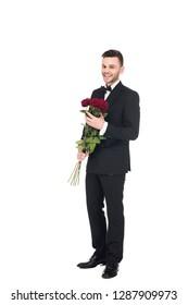 elegant man in black tuxedo holding red roses for valentines day, isolated on white