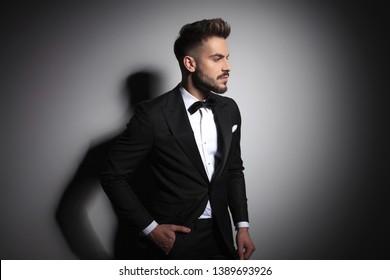 elegant man in black tuxedo standing with hands in pockets on grey studio background