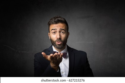 elegant man blowing kiss, dark background
