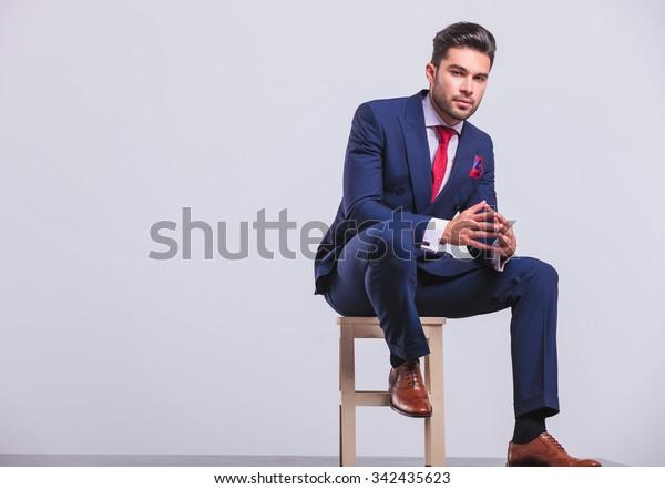 スタジオで座り、脚を椅子に乗せたまま手のひらを触れる優雅な男性