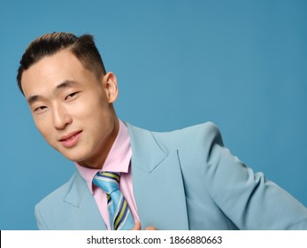 An elegant man in a classic suit on a blue background leaned to the side