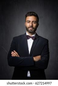 elegant man crossing arms, dark background