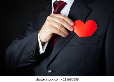 The elegant man in dark gray suit hiding a red heart into pocket