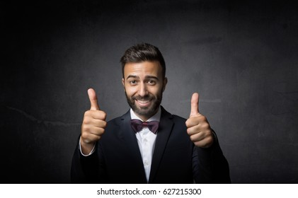 elegant man double thumbs up, dark background