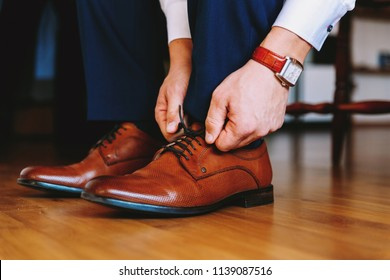 Elegant man dresses shoes. Two men's hands tie shoelaces. The man is wearing brown leather shoes and a white shirt and formal pants. I'm holding my watch. Male fashion.
