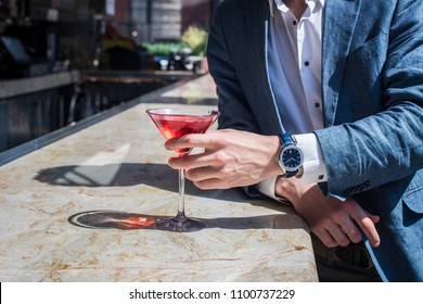 Elegant man drinking cocktails on the bar counter and waiting to date a girl