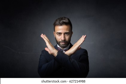 elegant man gesturing x with hands, dark background