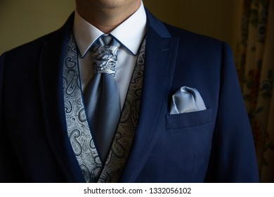 an elegant man getting dressed in the wedding suit