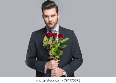 elegant man holding bouquet of red roses, isolated on grey