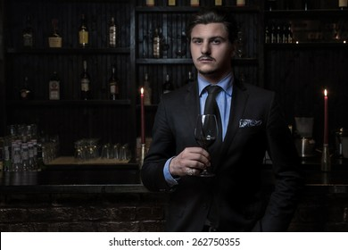 Elegant man holding a glass of wine