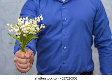 Elegant man holding lilies of valley. Gift on March 8