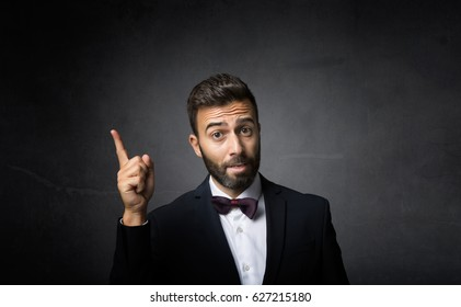 elegant man indicated with finger up, dark background