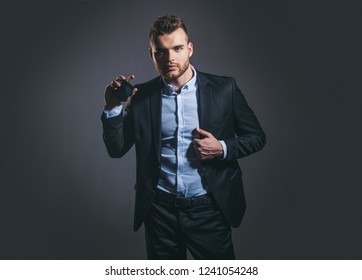 Elegant man for perfume. Masculine perfume. Fragrance. Male fragrance and perfumery, cosmetics. Man holding up bottle of perfumery. Mans perfume concept