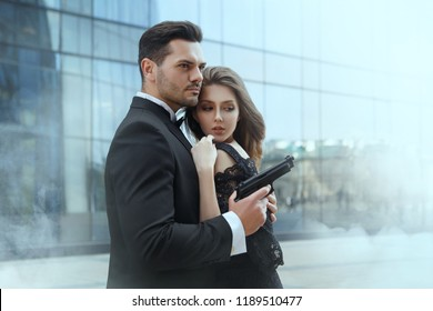 An elegant man with pistols in his hands protects a beautiful girl.