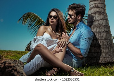 Elegant man man posing with his girlfriend on a beach