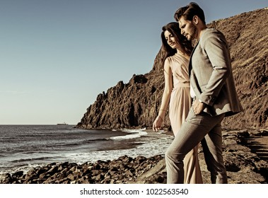 Elegant man man posing with his girlfriend on a beach