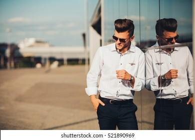elegant man posing in white shirt and watches
