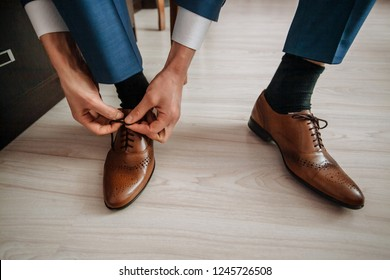 An elegant man puts on brown, leather, formal shoes. Tying shoes.