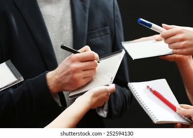 Elegant man signing autograph in notebook on dark background