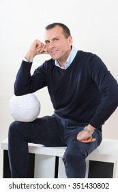 Elegant man sitting and looking in the camera, holding a football ball