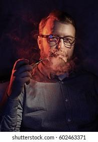 Elegant man smokes a pipe. Studio shot.