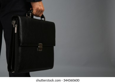 Elegant man in suit with briefcase on gray background