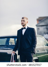 Elegant man in suit and butterfly tie near the car