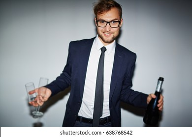 Elegant man in suit holding two flutes and bottle of champagne