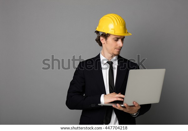 elegant man in suit with yellow protection helmet working at laptop for a project, on gray background