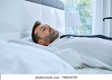 Elegant man taking nap in hotel room bed after business trip