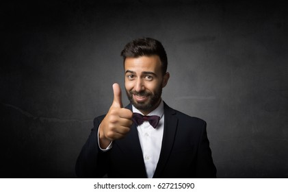 elegant man thumbs up, dark background