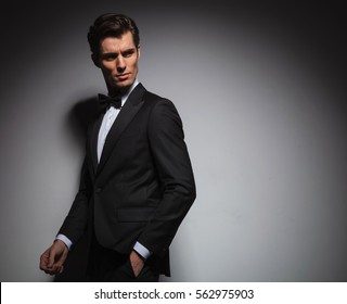 elegant man in tuxedo and bow tie walking with hand in pocket and looks back over his shoulder near grey studio background